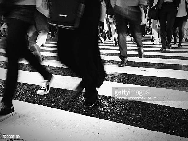 Low Angle View Of People Walking On Zebra Crossing Street