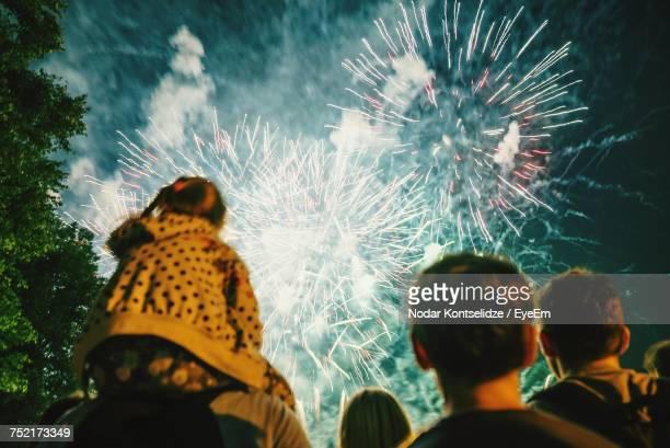 low angle view of people watching firework display - firework display stock pictures, royalty-free photos & images