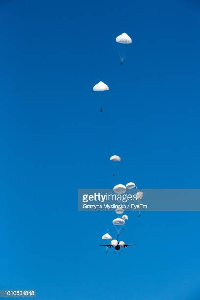 Low Angle View Of People With Parachute Against Clear Blue Sky