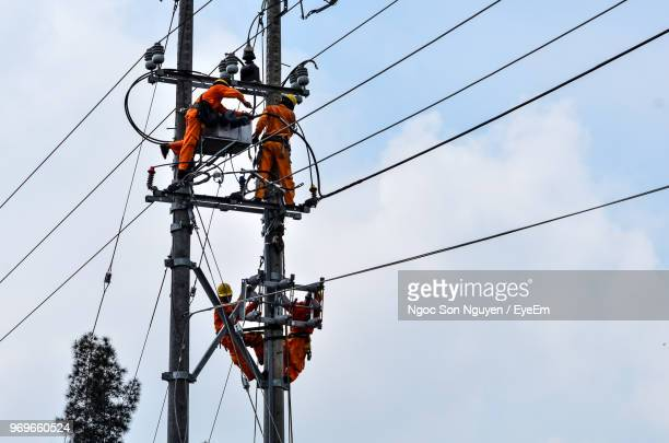 Low Angle View Of People Working On Electricity Pylon Against Sky