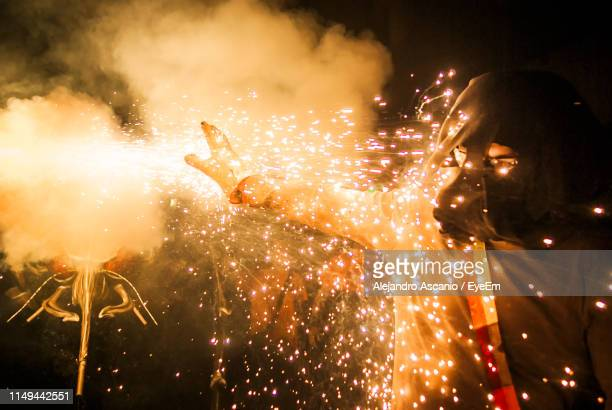 low angle view of person and firework display at night - alejandro ascanio fotografías e imágenes de stock