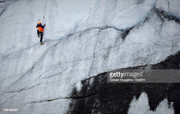 Low Angle View Of Person Climbing Snow Covered Rocky Mountain