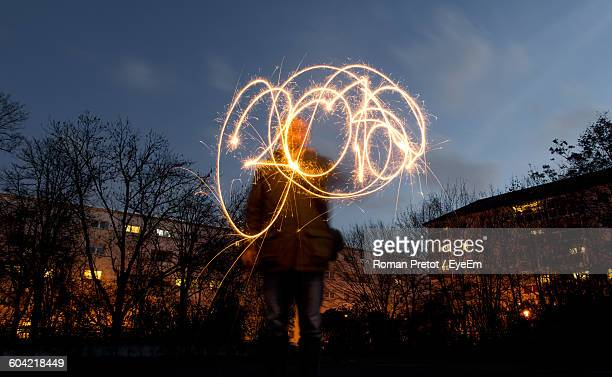 low angle view of person doing light painting at night - roman pretot stock-fotos und bilder