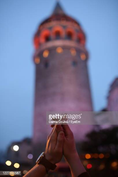 low angle view of person hand against illuminated building - istanbul stock pictures, royalty-free photos & images