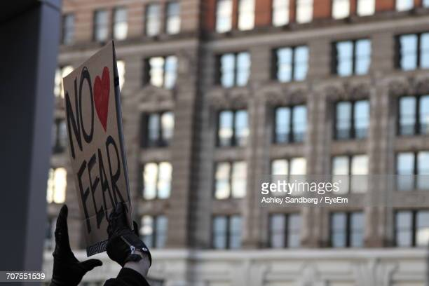 low angle view of person holding a protest billboard - demonstrant stockfoto's en -beelden