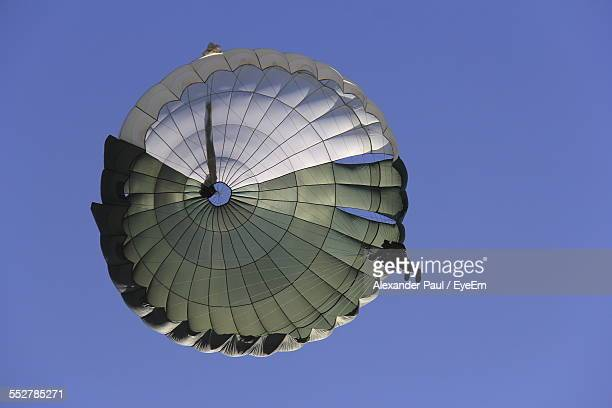 low angle view of person in parachuting against clear blue sky - fallschirm stock-fotos und bilder