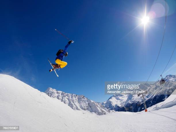 low angle view of person jumping on ski slope - wide angle stock pictures, royalty-free photos & images