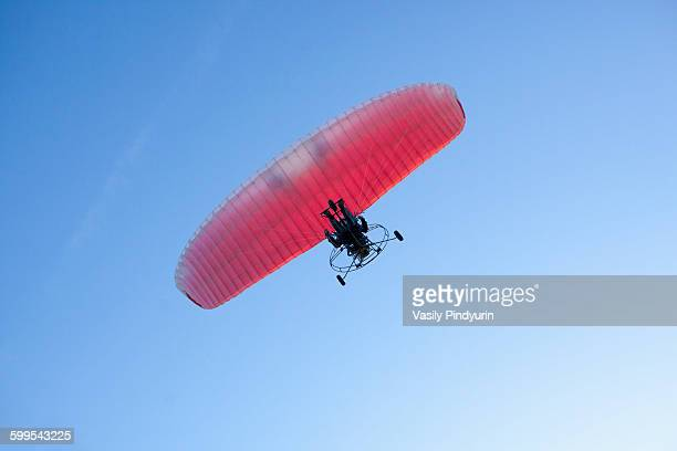 Low angle view of person motor paragliding against clear blue sky