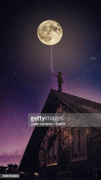 low angle view of person on roof against moon at night - optische täuschung stock-fotos und bilder