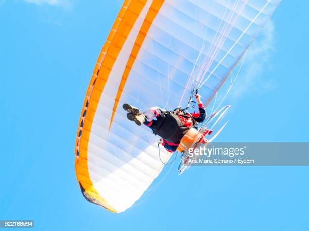 Low Angle View Of Person Paragliding Against Clear Blue Sky