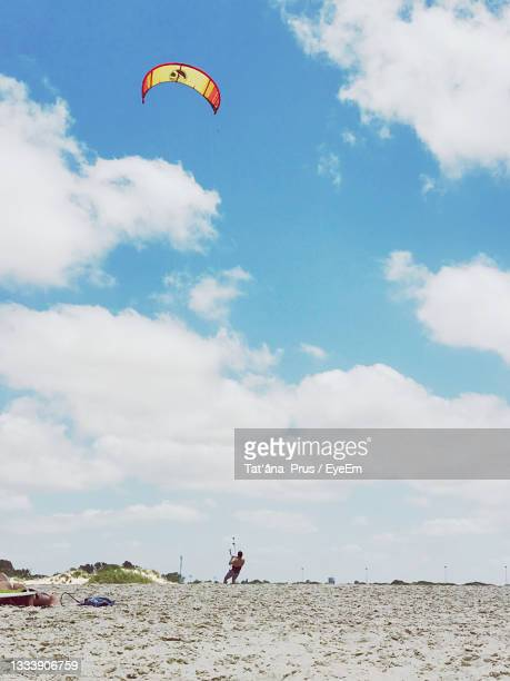 low angle view of person paragliding against sky - netanya stock pictures, royalty-free photos & images