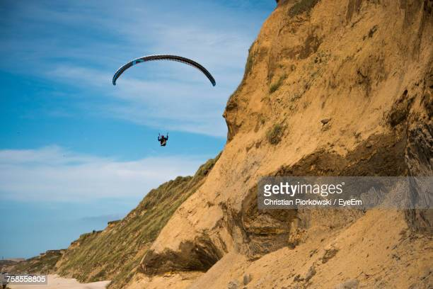 Low Angle View Of Person Paragliding By Rocky Mountains Against Sky