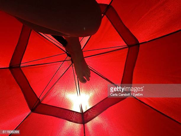 low angle view of person resting under beach umbrella - woman open legs stock photos and pictures