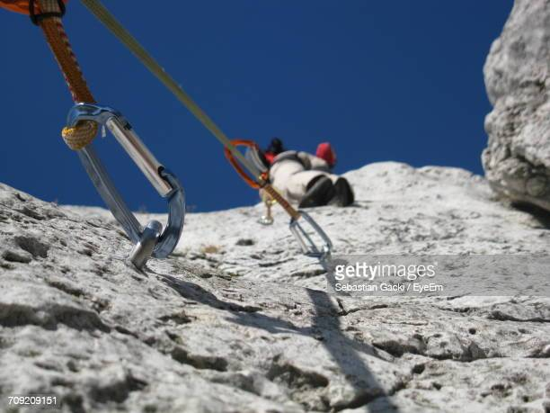 Low Angle View Of Person Rock Climbing Against Clear Sky