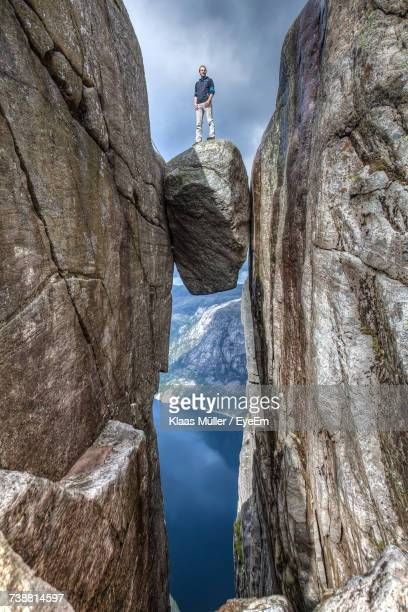 low angle view of person standing on cliff against sky - risque photos et images de collection