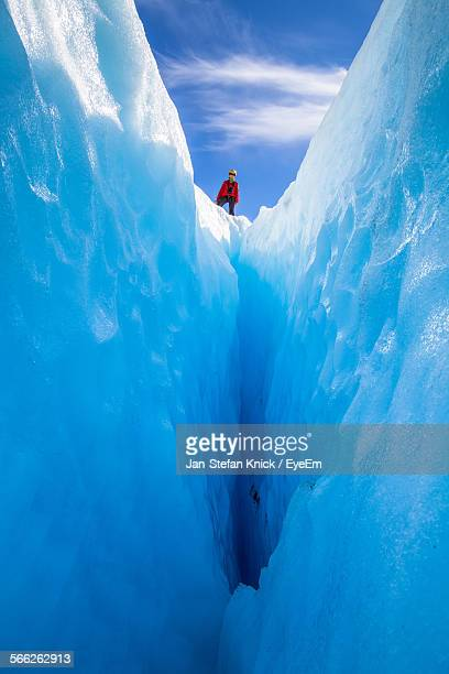 low angle view of person standing on glacier - crevasse stock photos and pictures