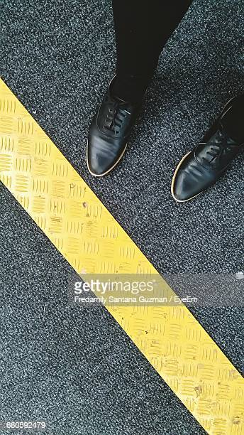 Low Angle View Of Person Standing On Road By Yellow Dividing Line