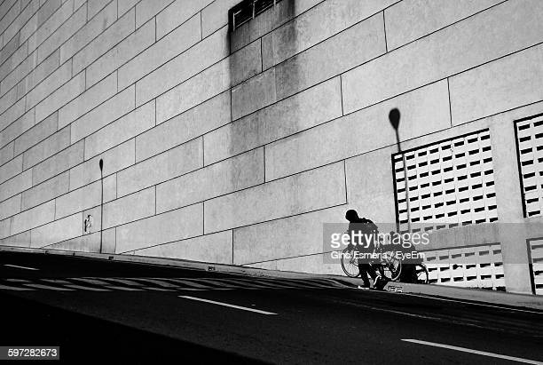 Low Angle View Of Person With Bicycle Walking On Street By Wall