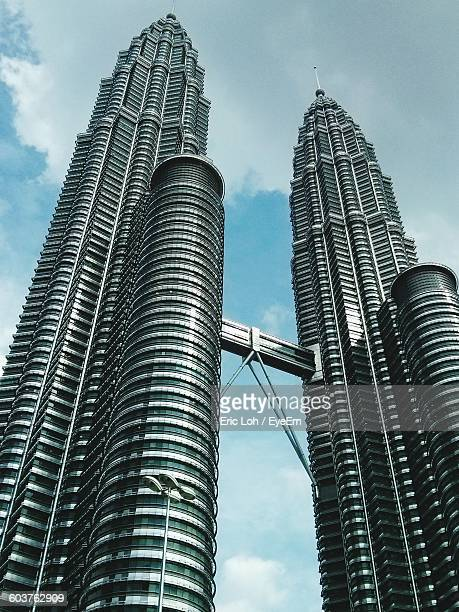 low angle view of petronas towers against sky - petronas towers stock pictures, royalty-free photos & images