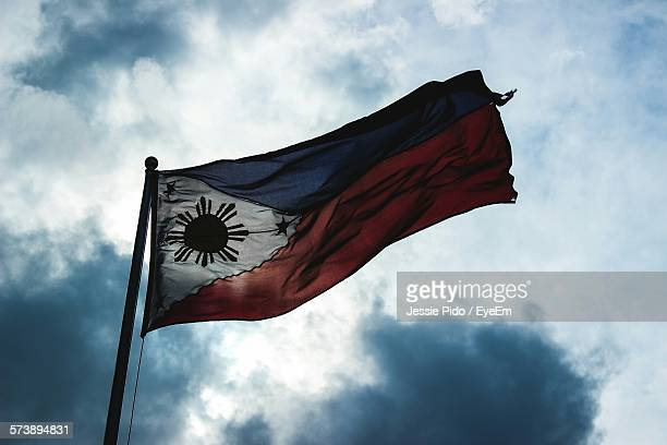 low angle view of philippines flag against cloudy sky - philippines flag stock pictures, royalty-free photos & images