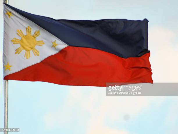low angle view of philippines flag against sky - philippines flag stock pictures, royalty-free photos & images