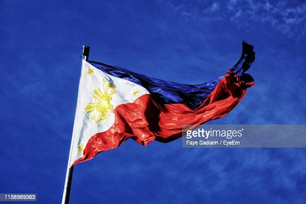 low angle view of philippines flag waving against blue sky - philippine independence day stock pictures, royalty-free photos & images