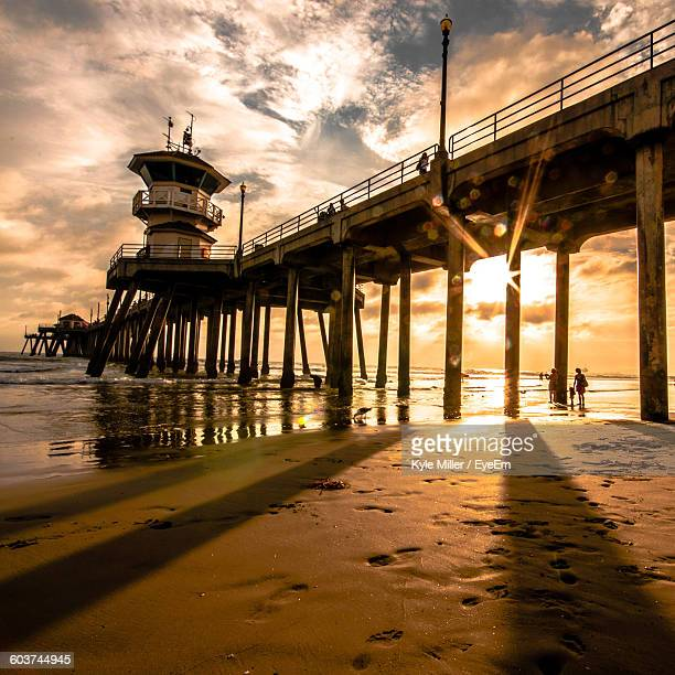 Low Angle View Of Pier At Beach Against Sky During Sunset