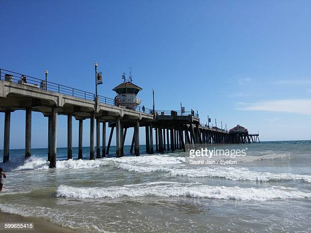 Low Angle View Of Pier At Beach Against Sky On Sunny Day