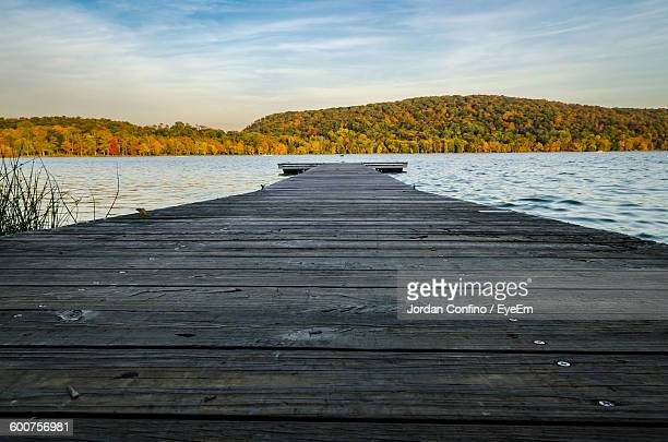 Low Angle View Of Pier On Lake By Mountain Against Sky