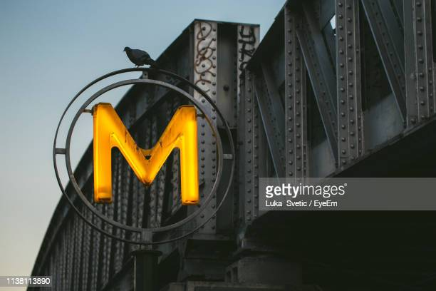 low angle view of pigeon perching on illuminated letter m against sky - letter m stock pictures, royalty-free photos & images