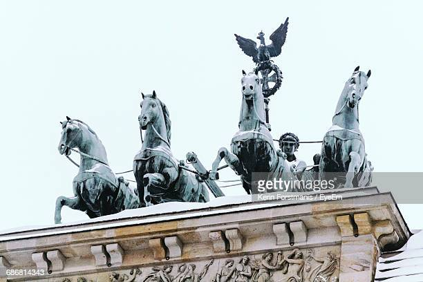 Low Angle View Of Pigeons Perching On Statue