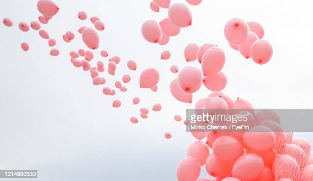 low angle view of pink balloons against sky - 風船 ストックフォトと画像