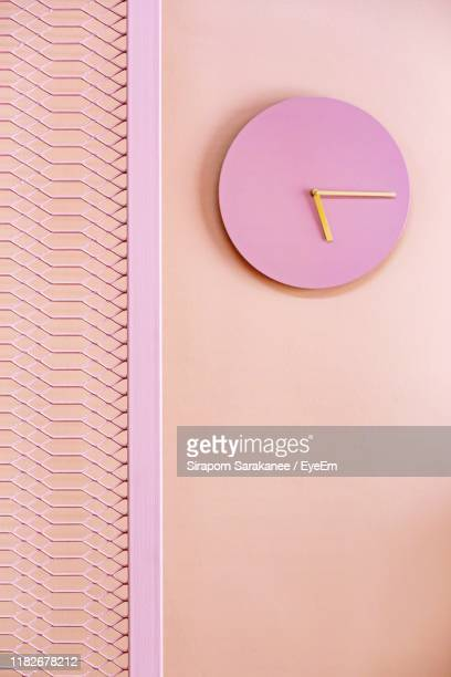 low angle view of pink clock on wall - wall clock stock pictures, royalty-free photos & images