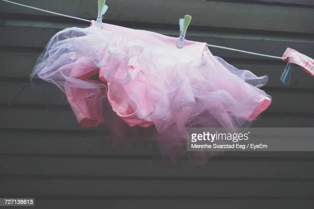 Low Angle View Of Pink Dress Hanging From String Against Wall