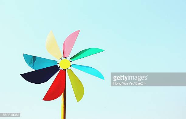 low angle view of pinwheel toy against cloudy sky - paper windmill stock photos and pictures