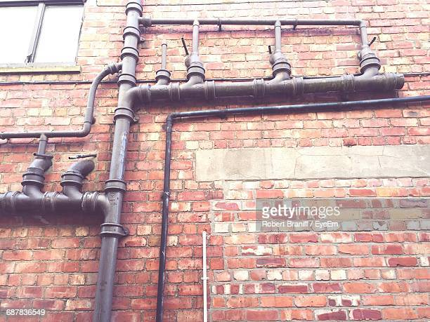 low angle view of pipeline on brick wall - モーペス ストックフォトと画像