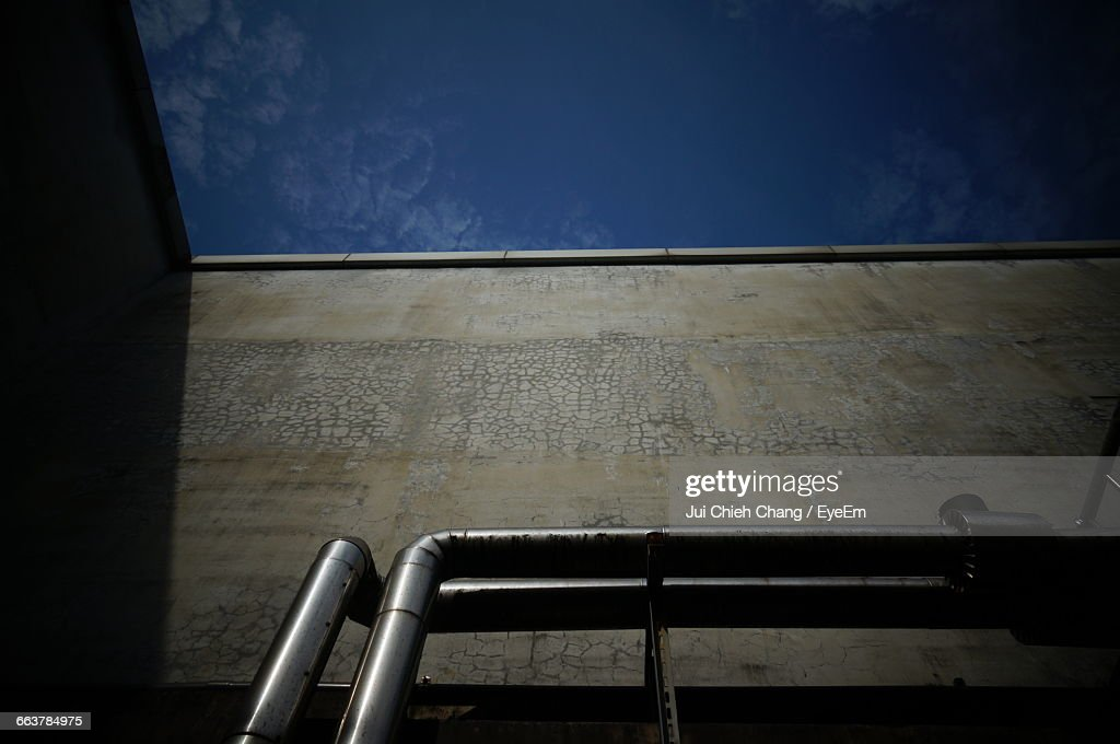 Low Angle View Of Pipes And Buildings Against Sky : Stock Photo