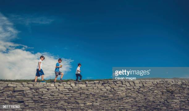 low angle view of playful brothers walking on stone wall against sky - kingston ontario stock photos and pictures