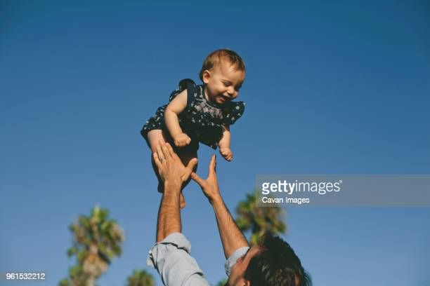low angle view of playful father throwing daughter in air against clear blue sky - throwing stock pictures, royalty-free photos & images