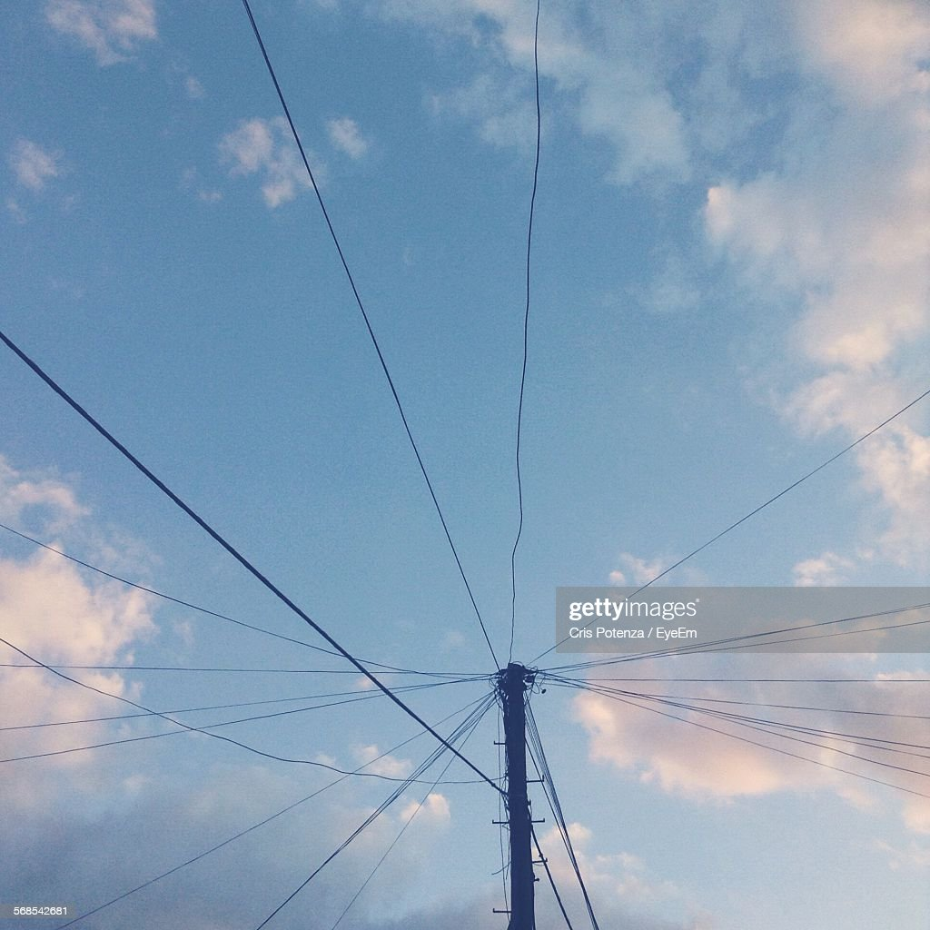Low Angle View Of Pole With Power Lines Against Cloudy Sky : Stock Photo