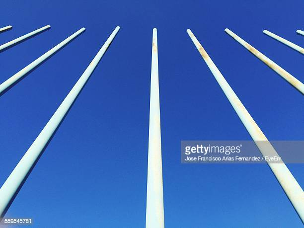 Low Angle View Of Poles Against Clear Blue Sky