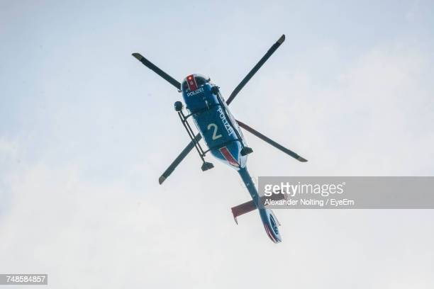 Low Angle View Of Police Helicopter Flying Against Sky