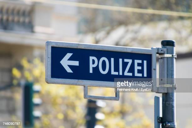 Low Angle View Of Police Sign With Arrow Symbol
