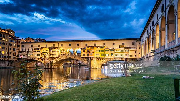 Low Angle View Of Ponte Vecchio Over Arno River Against Cloudy Sky
