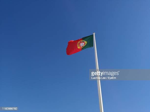 low angle view of portuguese flag against clear blue sky - lucinda lee stock photos and pictures