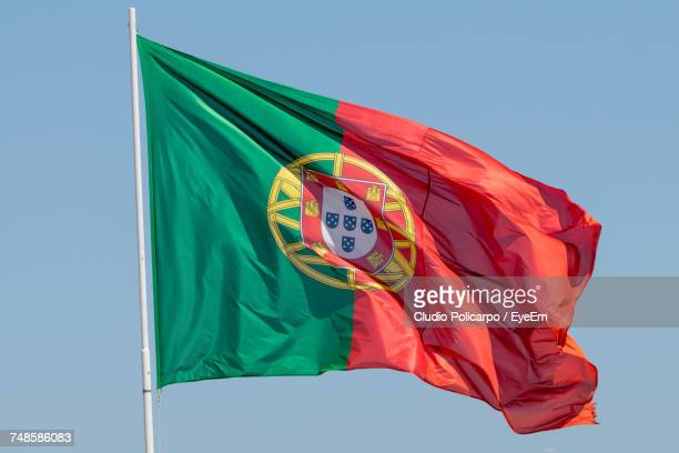 low angle view of portuguese flag against sky - national flag stock photos and pictures