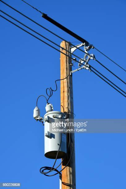 Low Angle View Of Power Line Against Clear Blue Sky