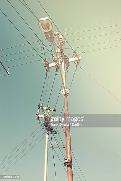 low angle view of power lines against clear sky - frank swertz stockfoto's en -beelden
