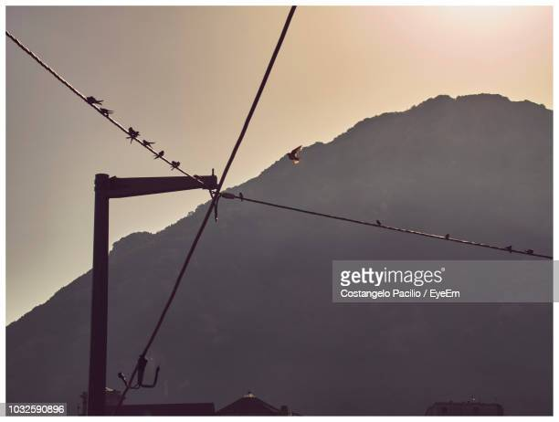 low angle view of power lines and mountains against sky at sunset - costangelo pacilio foto e immagini stock