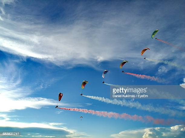 Low Angle View Of Powered Parachutes With Colorful Vapor Trails Against Sky During Airshow